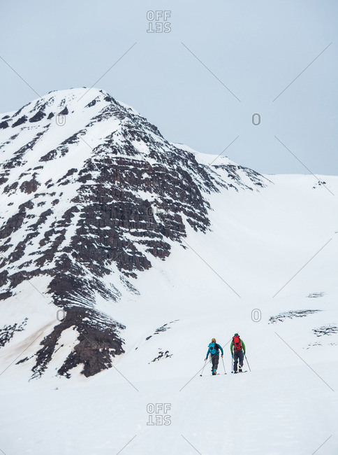 A man and a woman backcountry ski in Iceland