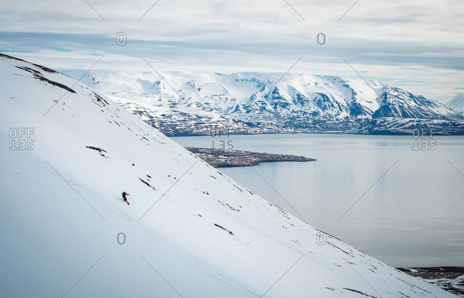 A man skiing down a mountain with snowy mountains and ocean behind