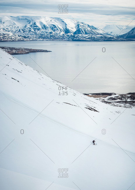 A man skiing downhill with ocean and mountains in the background