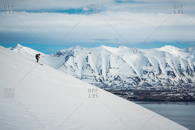 A woman skiing downhill with ocean and mountains in the background