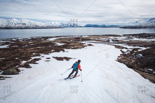Woman skiing towards the ocean in Iceland