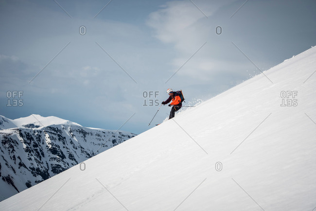 Man skiing downhill in Iceland with mountains behind