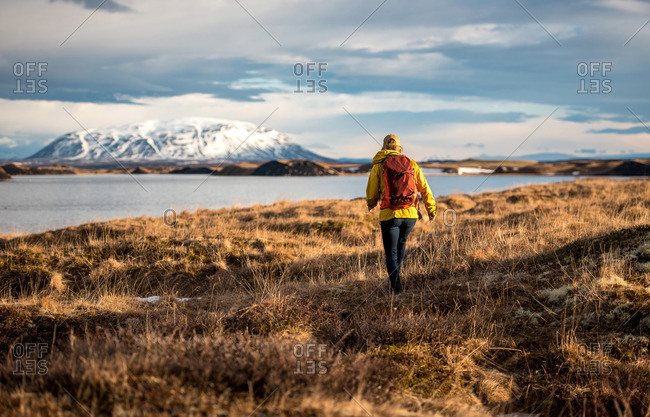 Woman hiking with backpack along lake in Iceland