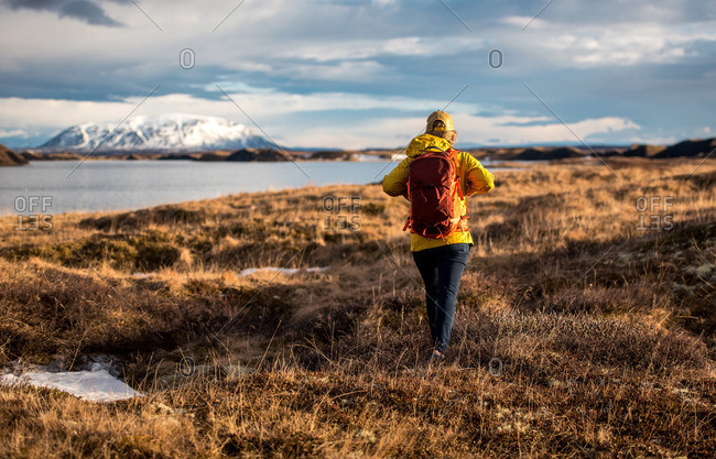 Woman walking away from camera with backpack next to lake