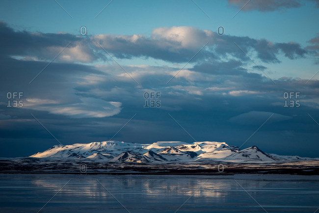 Mountains alongside a lake in Iceland with moody clouds
