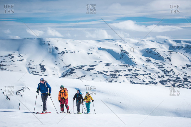 A group of skiers touring in snowy mountains in Iceland