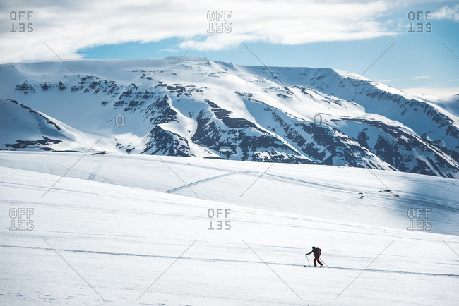 Man backcountry skiing on ski tracks with mountain in background