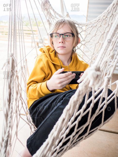 Portrait of tween in hammock listening to music