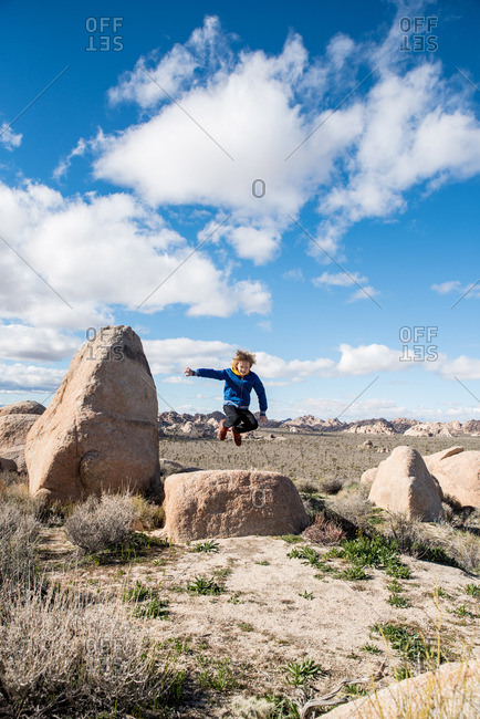 Teenager jumping off large stone in Joshua Tree National Park