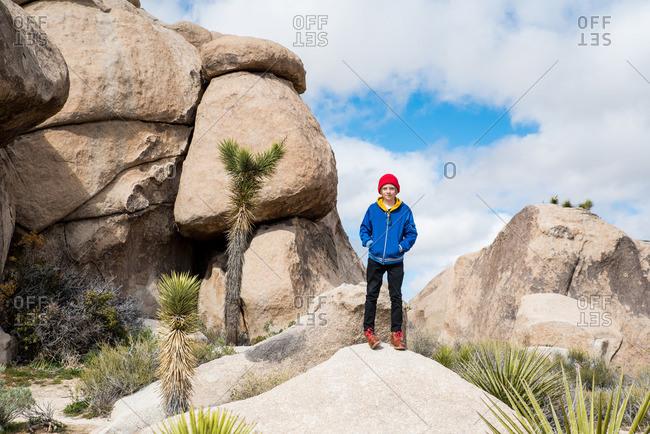 Tween standing on stones in Joshua Tree National Park