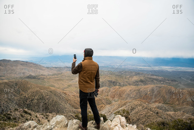 Man using phone on hill showing desert valleys below under gray sky