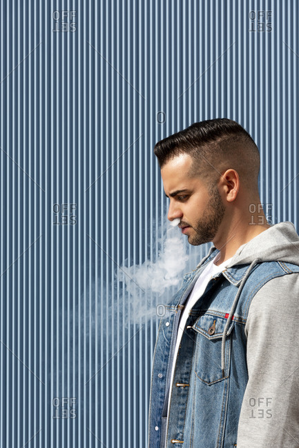 Young man smoking with an electronic cigarette over blue background