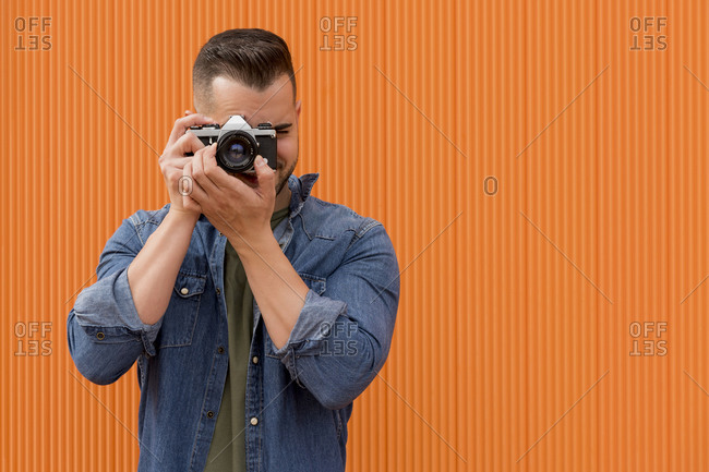 Portrait of a young man taking a photograph