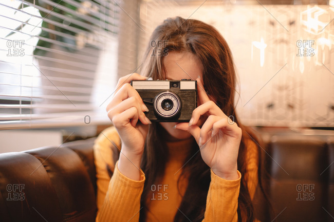 Teenage girl photographing with vintage camera while sitting in cafe