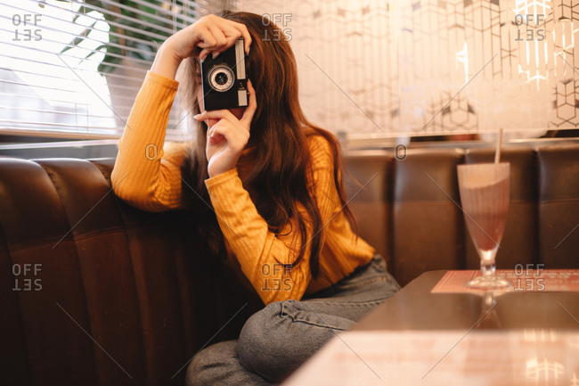 Young woman photographing with vintage camera while sitting in cafe