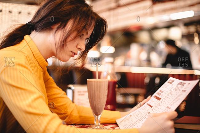 Teenage girl reading menu while sitting in restaurant