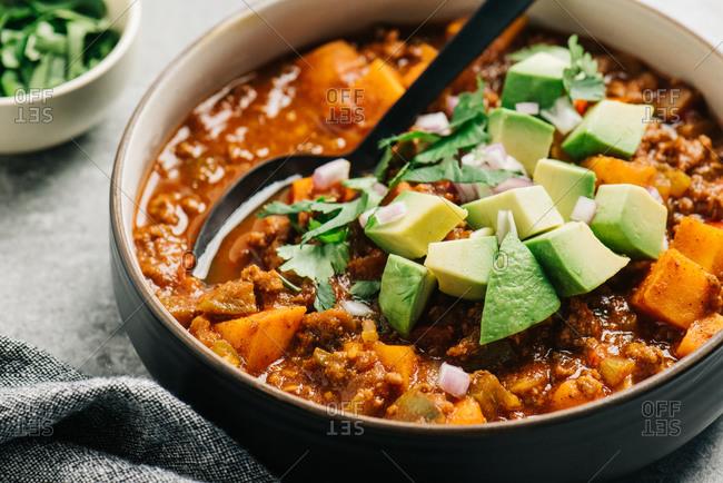 Paleo chili con carne closeup with fresh cilantro and avocado