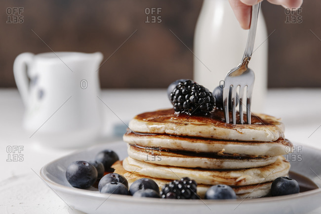 Woman sticking a fork into a stack of homemade pancakes
