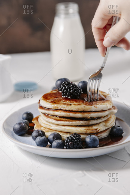 Woman sticking a fork into a stack of homemade pancakes with berries