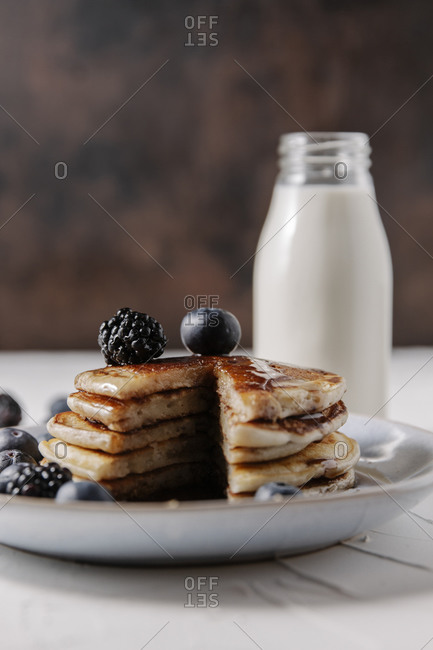 Still life of a stack of homemade pancakes with berries and syrup on a plate, and a bottle glass of milk in background.
