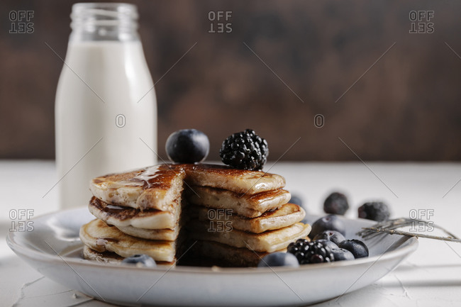 Still life of a stack of homemade pancakes with berries and syrup