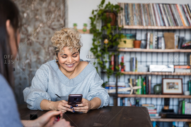 Smiling woman text messaging on smart phone while sitting with friend at home