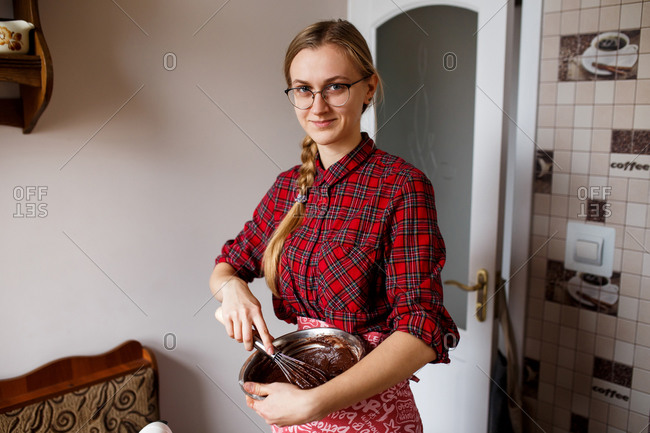 The process of mixing and preparing chocolate cupcakes by young lady