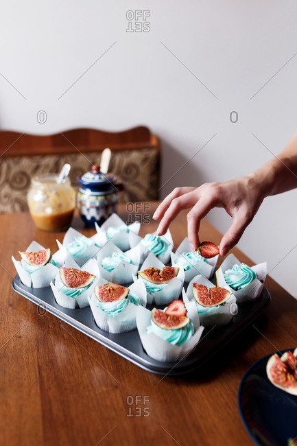 Decorating Homemade Chocolate  Muffins With Blue Cream Topping And Fig