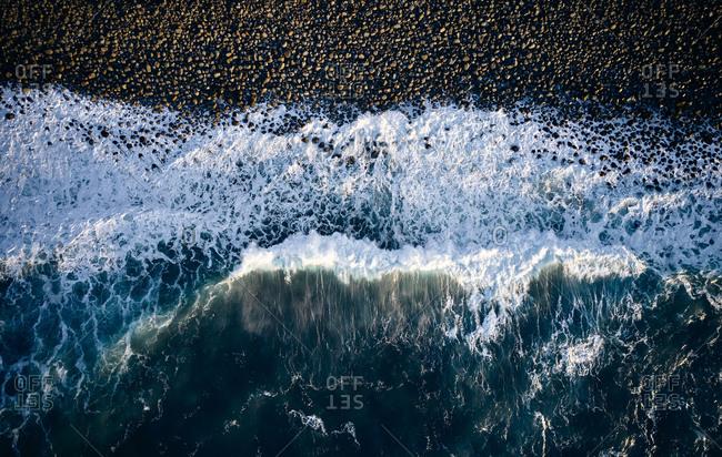 Waves crashing over stone beach