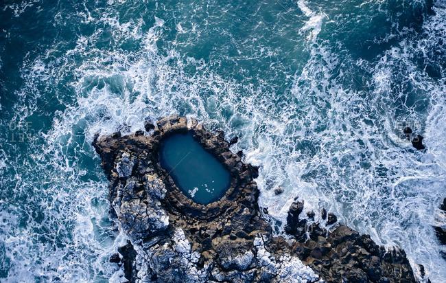 Waves crashing over rocks in sea