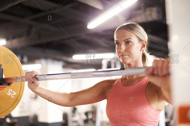 A portrait of a blonde woman lifting weights in the gym.