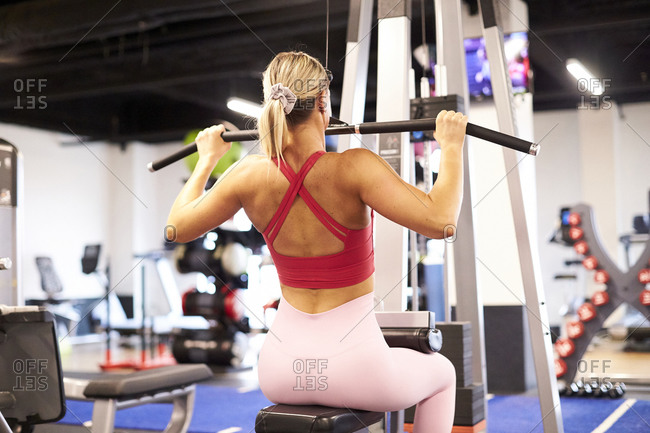A back view of a woman working out in the gym.