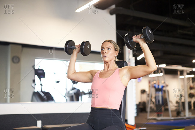 A woman lifting weights in a fitness studio.