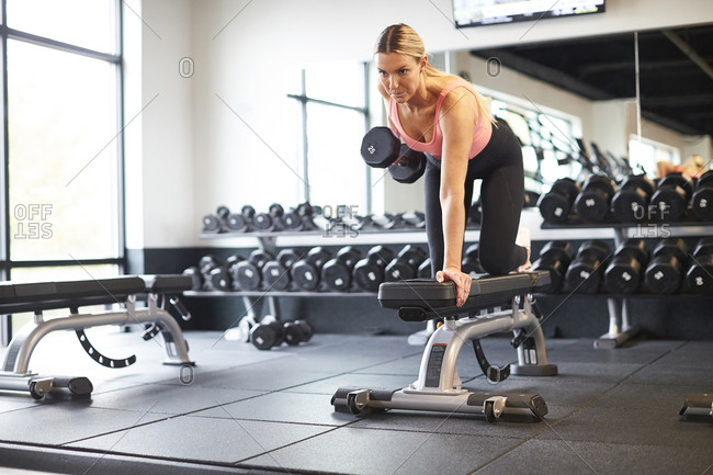 A woman exercising with weights in a gym.