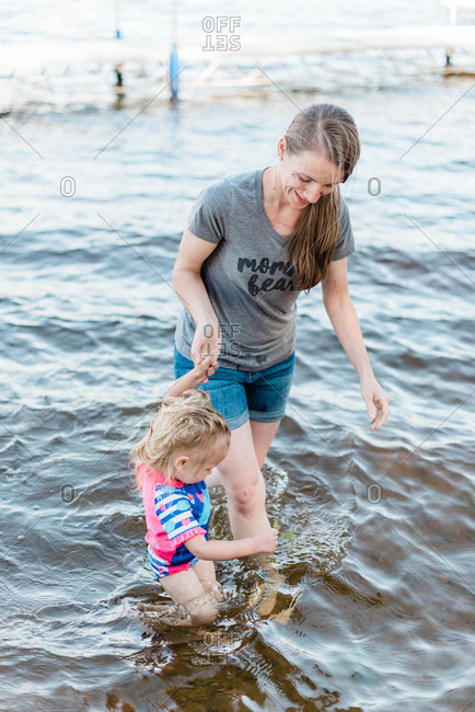 A mother and her daughter cooling off at the lake.