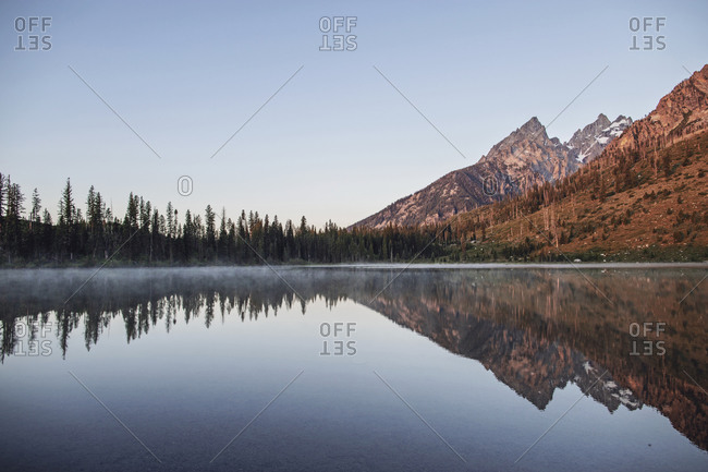 Tetons reflected in the still waters of String Lake at sunrise