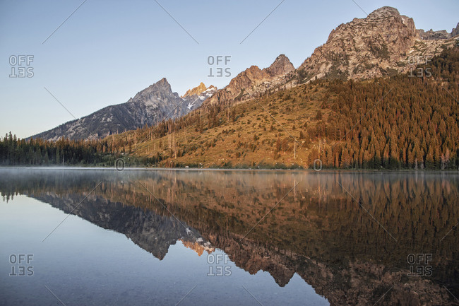 Tetons at sunrise reflected in still waters of String Lake, Wyoming