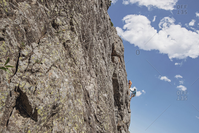 Two people cling to the side of a cliff while rock climbing, Wyoming