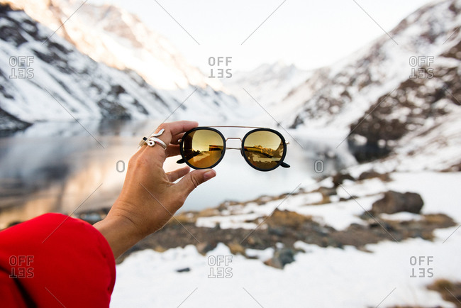A tourist holds up a pair of stylish sunglasses in the mountains