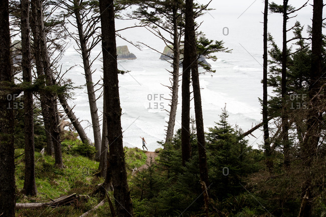Cannon Beach, Oregon - May 1, 2018: A solo traveler takes in the scenic coastline view