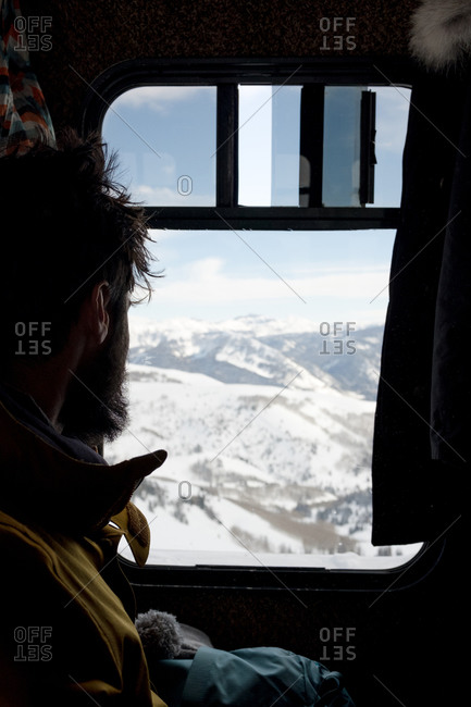 Male skier enjoys the view of fresh powder on a sunny winter day