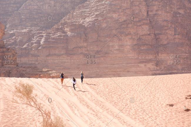 Three friends sprint to the horizon of the Wadi Rum desert in Jordan.