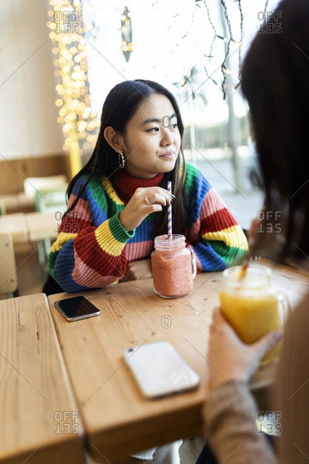 Two best friends having  smoothies at a cafe in the city