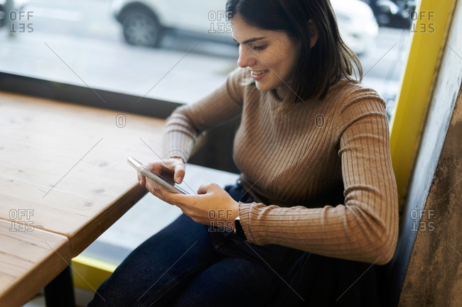 Young freckles woman using smart phone sitting by the window