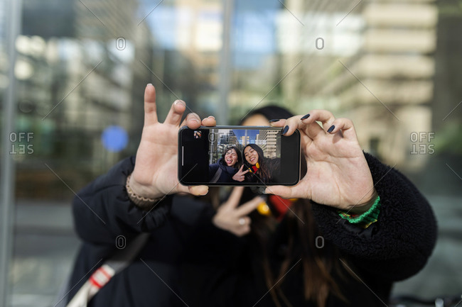 Girls taking a selfie on mobile phone and showing photo at camera