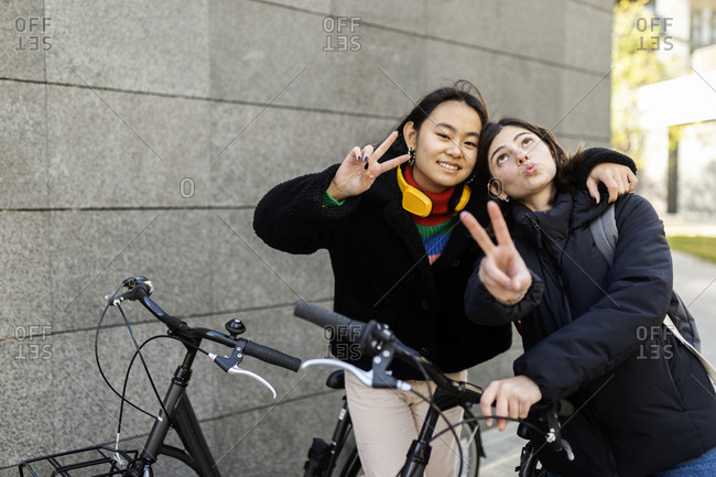 Two best friends showing victory sign while holding bicycles