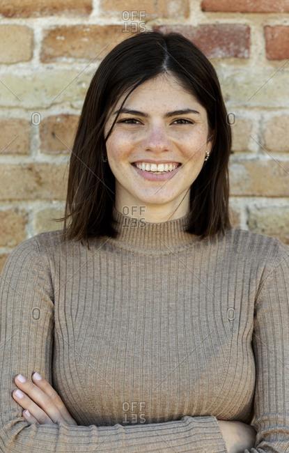 Freckles young brunette woman portrait against brick wall