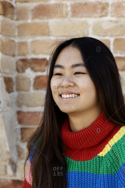 Happy young Asian woman portrait against brick wall