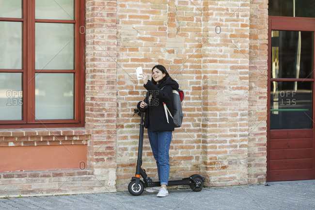 Young woman riding scooters and taking a selfie