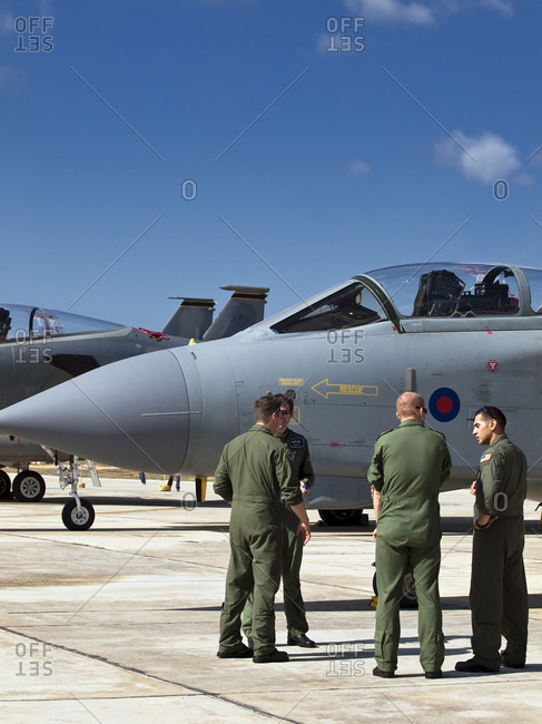 Luqa, Malta - September 26, 2009: American and British fighter jet pilots have a friendly chat on apron